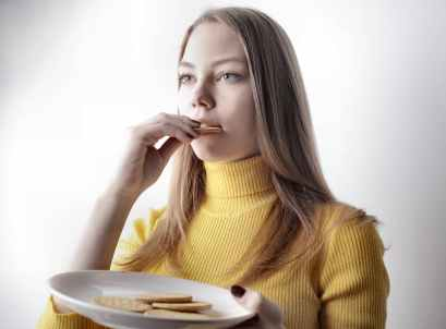 woman in yellow sweater holding white ceramic plate