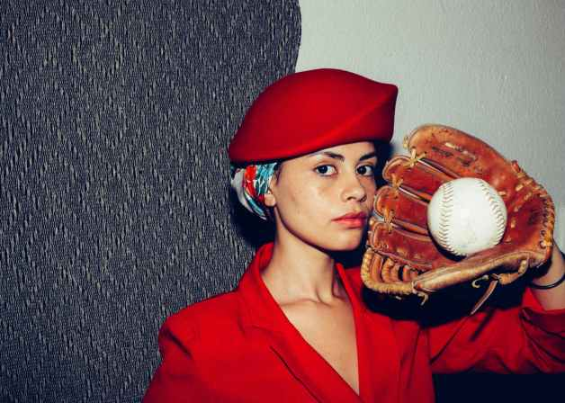 woman in red cap while wearing baseball glove