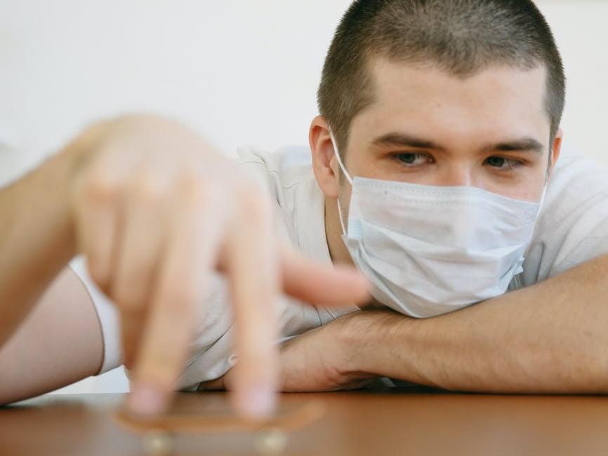man wearing face mask playing finger skateboard